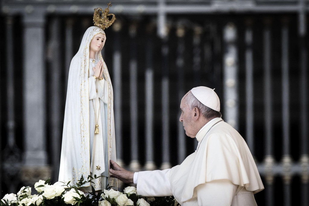 Pope Francis touches a statue of Our Lady of Fatima as he arrives for his weekly general audience in St. Peter's Square, Vatican City, 13 May 2015. ANSA/ANGELO CARCONI