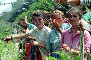 ** FILE ** A July 13, 1995 file photo shows refugees from the overrun U.N. safe haven enclave of Srebrenica looking through the razor-wire at newly arriving refugees in a UN base 12 kms south of Tuzla, 100kms (60 miles) north of Sarajevo.Former Bosnian Serb leader Radovan Karadzic, accused architect of war crimes including Europe's worst massacre since World War II, was arrested Monday evening, July 21, 2008 the country's president and the U.N. tribunal for the former Yugoslavia said. Karadzic topped the tribunal's most-wanted list for more than a decade charged with organizing the deadly siege of Sarajevo and the 1995 massacre of up to 8,000 Muslims in the U.N. 'safe area' Srebrenica. (AP Photo/Darko Bandic, File)