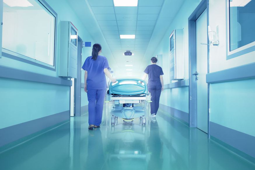 web-hospital-care-nurses-corridor-bed-shutterstock_131191718-sfam_photo-ai